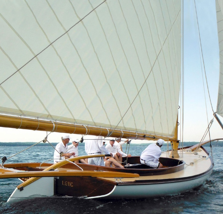 A group of men sailing a custom hand made Van Dam sailing boat.